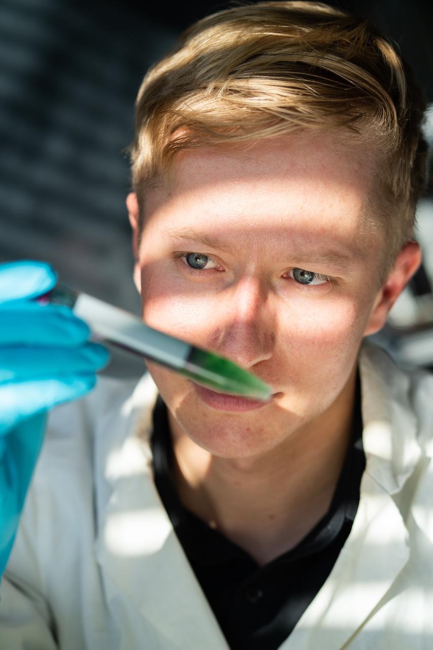Johann Bauerfeind betrachtet ein Reagenzglas mit Flüssigkeit und Algen