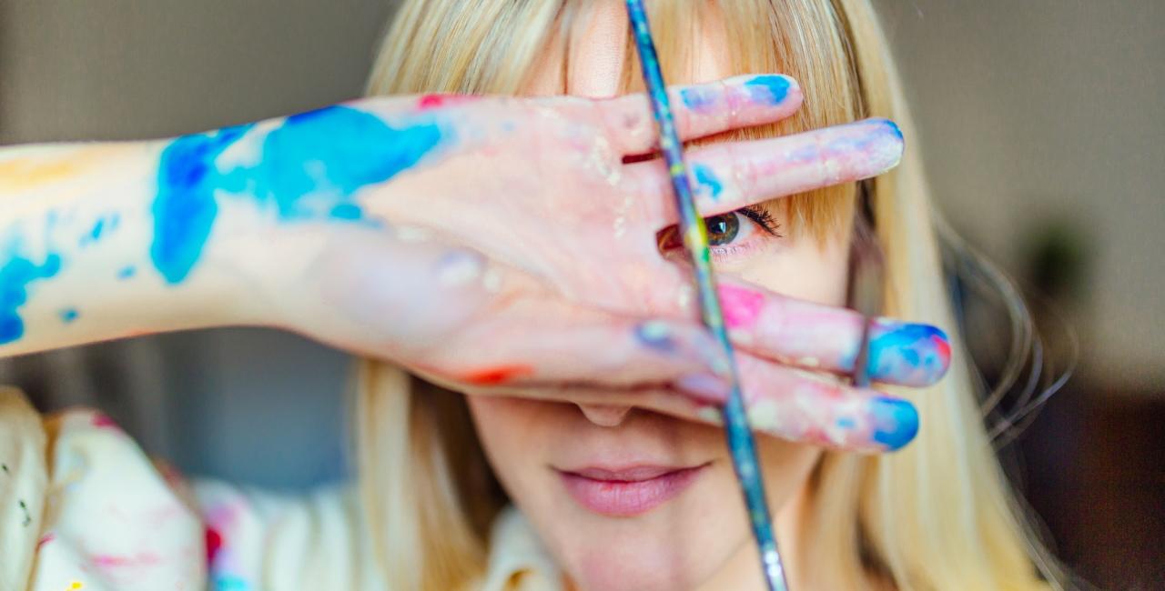Frau hält sich ihre Hand mit einem Pinsel vors Gesicht, Farbe an ihren Händen und ihrem Kittel