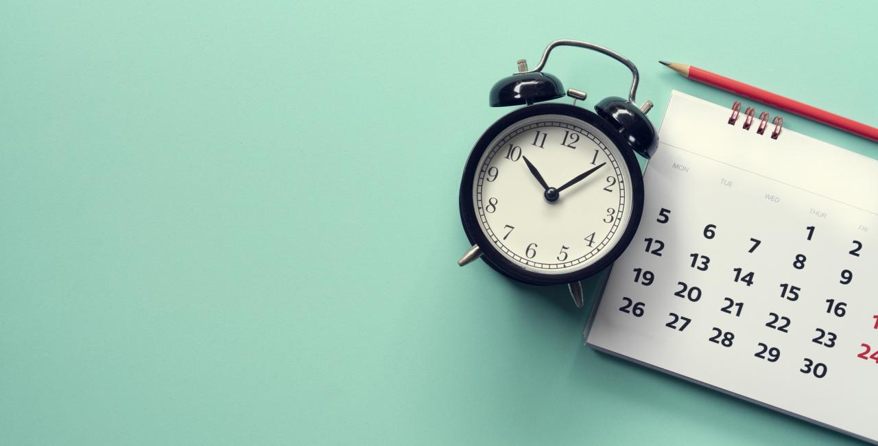 Kalender und Wecker auf dem grünen Hintergrund