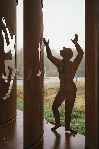 Stahlfiguren, die eine Stahlmauer überwinden und durchdringen