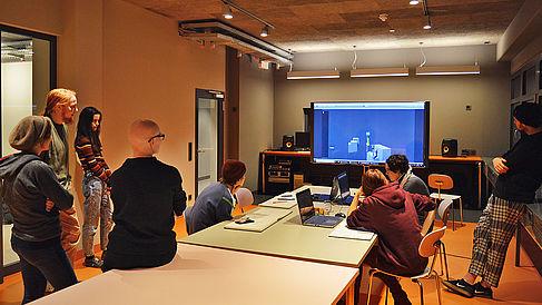 Studierende betrachten gemeinsam einen Bildschirm.