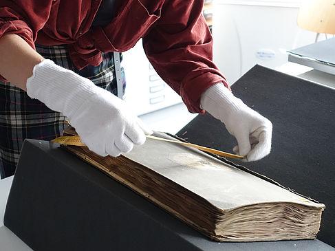 Ein Farbrezeptbuch wird sorgfältig ausgemessen