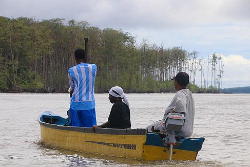 Muschelsammler_innen bei der Fahrt mit einem Boot mit Elektromotor
