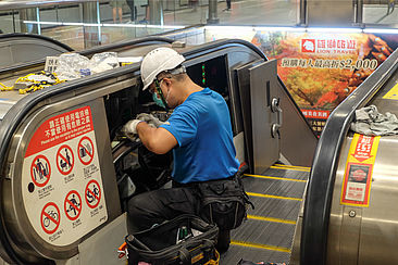 Mann repariert eine Rolltreppe