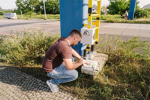Projektmitarbeiter kniet an einem Sensorgehäuse.