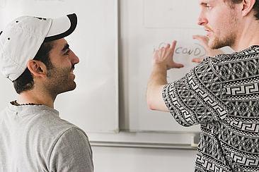 Tobias Winslow erklärt einem Geflüchteten, wann man welche Programmiersprache einsetzt