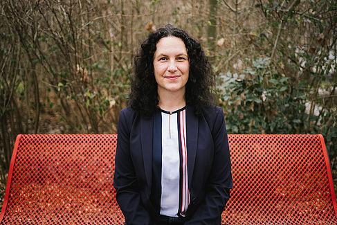 Dr Lena Simon auf einer roten Bank sitzend
