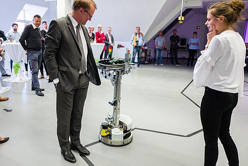 HTW-Präsident Klaus Semlinger testet die Fähigkeit des mobilen Roboters, Hindernisse zu erkennen.