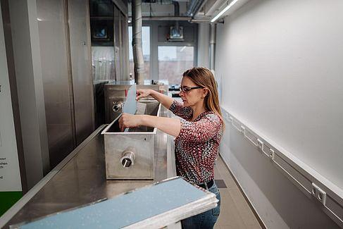 Simone Brandt platziert ein Bodenbelagsmuster in einer Edelstahlbox