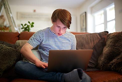Junger Mann mit Downsyndrom vor einem Laptop