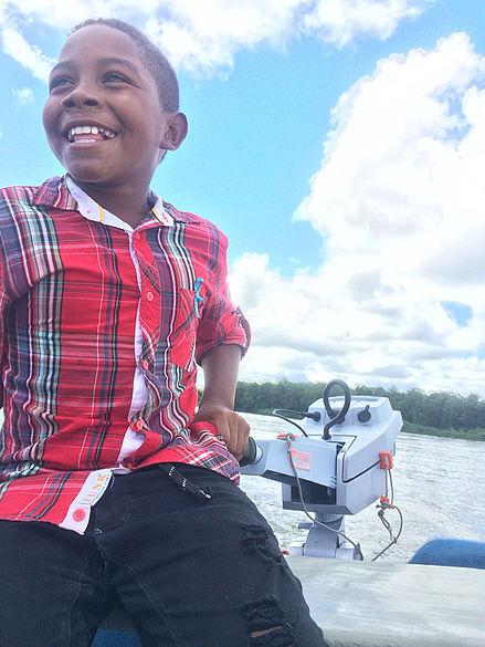 Lächelnder Junge bedient in einem Boot den Elektromotor