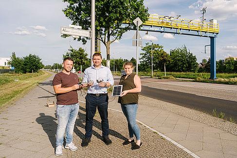 Drei Personen halten Sensoraufbauten und ein Solarmodul in der Hand.