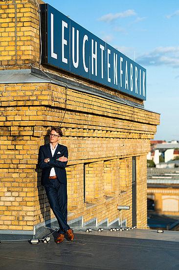 Stefan Otto neben dem Signet der Leuchtenfabrik
