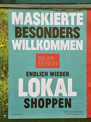 """Plakat mit der Aufschrift """"Maskierte besonders willkommen. Bikini Berlin. Endlich wieder lokal shoppen."""""""