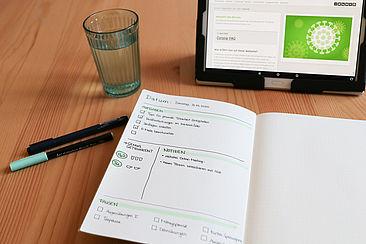 Arbeitsplatz mit Kalender, Wasserglas und Laptop