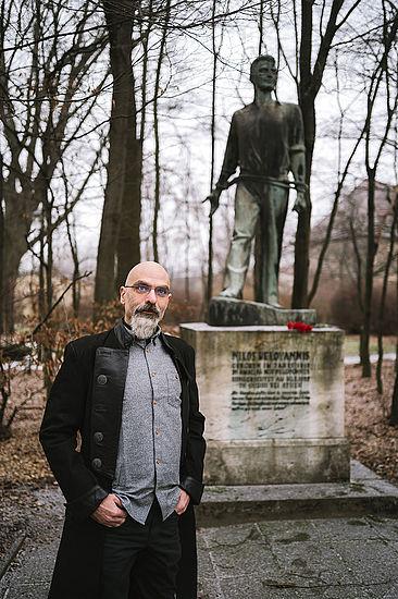 Prof. Dr. Dimitrios Zikos vor einem Personendankmal