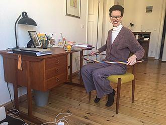 Stefanie Molthagen-Schnöring sitzend mit Hula-Hoop-Reifen am Schreibtisch
