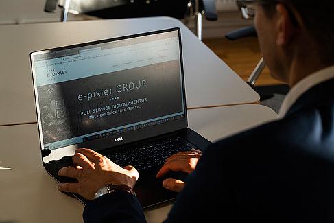 Stefan Otto blickt auf einen Laptop, der die Webseite seiner Internetagentur zeigt