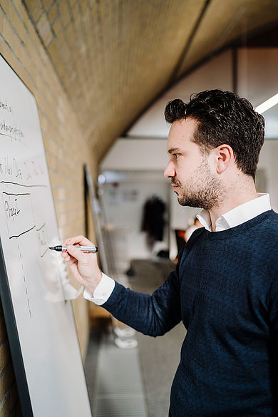 Gründer Tim Wegner schreibt etwas auf ein Whiteboard