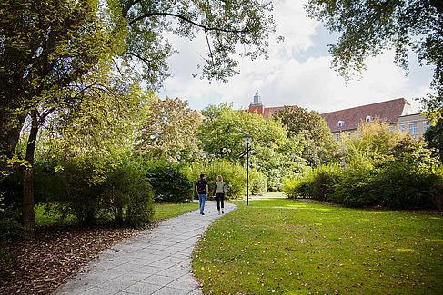 Zwei Studierende laufen einen Weg auf dem grünen Campus Treskowallee entlang
