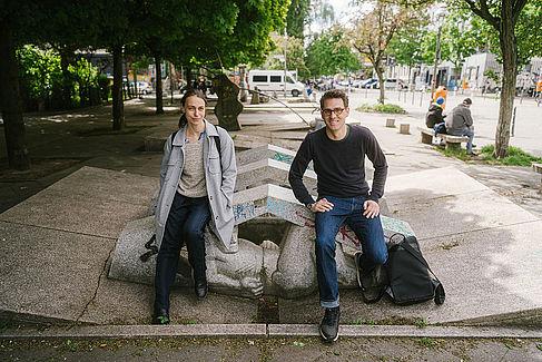 Nada Bretfeld (links) und Prof. Dr. Florian Koch sitzen auf einem Stein