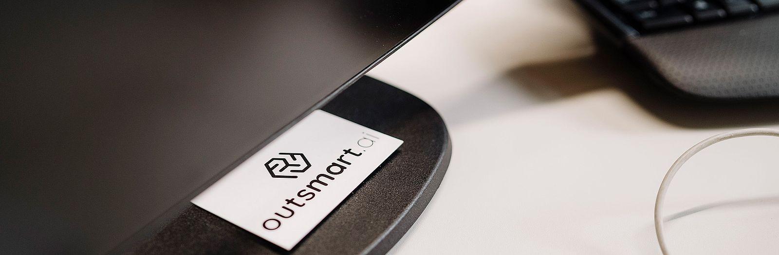 Das Logo von outsmart.ai auf einer Visitenkarte