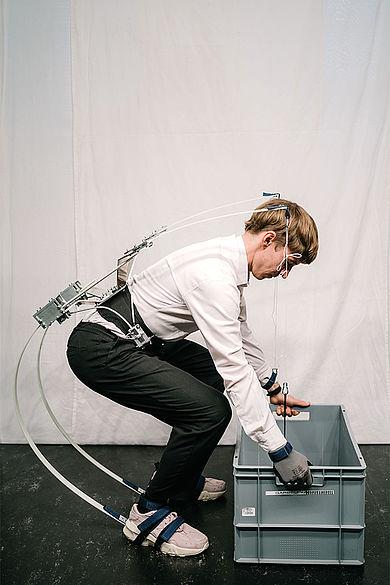 Mann mit Exoskelett bückt sich und hält eine Kiste mit beiden Händen
