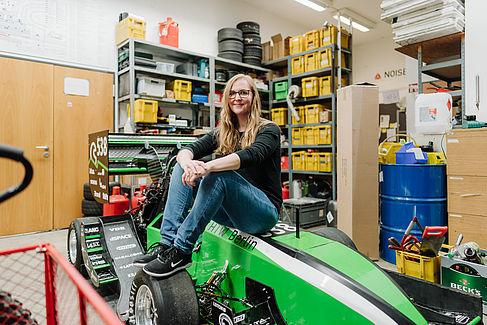 Susanne Nelke sitzt auf dem Rennwagen des HTW-Motorsport