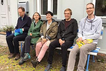 Fünf Menschen sitzen auf einer Bank