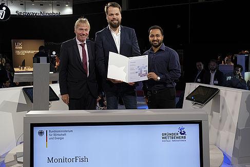 """Preisträger beim """"Gründerwettbewerb - Digitale Innovationen"""": Dr. Andreas Goerdeler (BMWi) mit Dominik Ewald und Chaitanya Dhumasker (von links nach rechts)."""