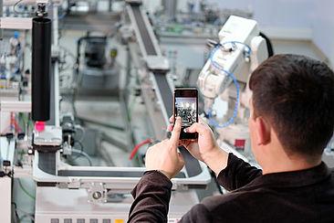 Mann mit Smartphone vor Maschine