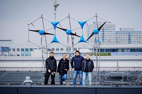 Vier Männer auf einem Dach vor einer Windenergieanlage