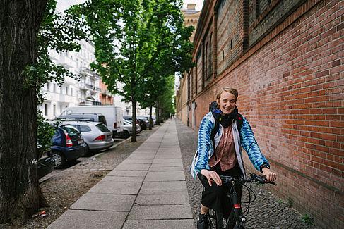 Laura Tihon auf dem Fahrrad, mit Airbag um den Hals